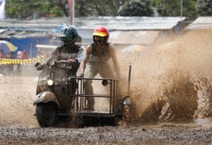 Participants ride in a Vespa-cross race