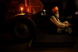 A farmer rests beside his tractor. Protest leaders have rejected the government's offer to amend some contentious provisions of the new farm laws