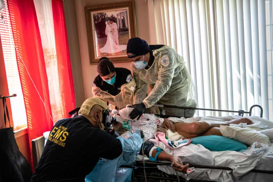 Medics intubate a gravely ill patient with Covid-19 symptoms at his home in Yonkers, New York, on 6 April 2020.