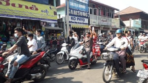 People on motorcycles raise a three-finger salute as they take part in a protest against the military coup, in Dawei