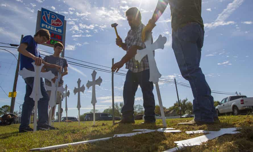 People hammer in crosses at the VP Racing Fuels gas station just down the road from the First Baptist church of Sutherland Springs.