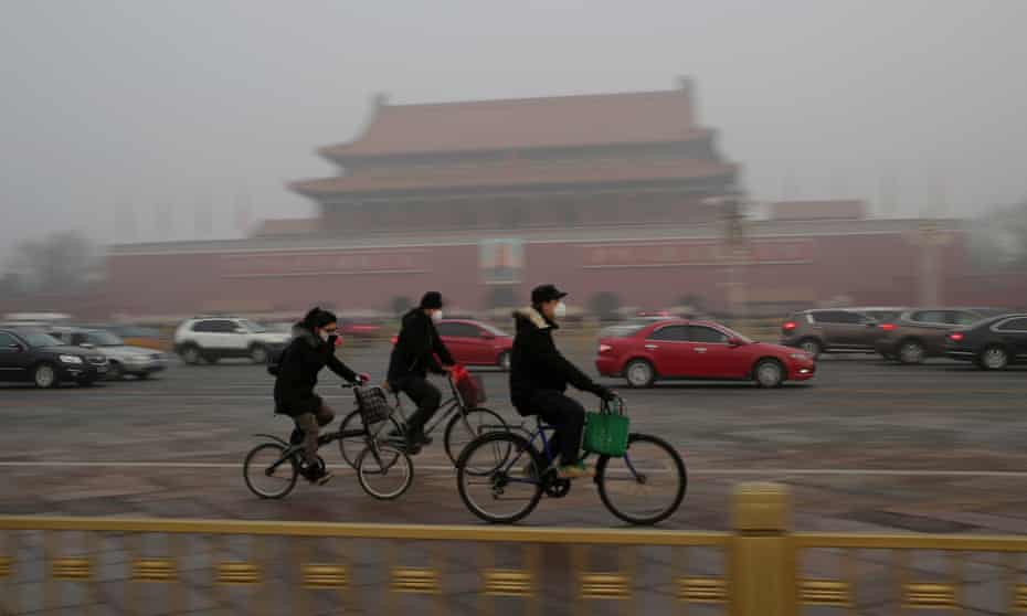 People wearing masks cycle through smog in Tiananmen Square during a red alert for heavy air pollution in Beijing.