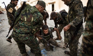 Syrian Democratic Forces (SDF) fighters help a shell shocked SDF fighter on his feet.