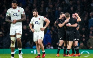 New Zealand's players celebrates at the final whistle as England players react to a narrow defeat.