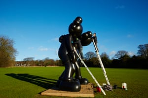 Staff polishing Along the Way (2015) one of the sculptures by American artist KAWS
