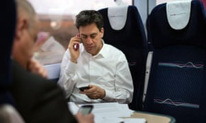 Ed Miliband uses two phones as he travels by train to Plymouth to visit businesses