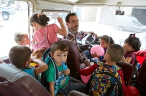 Pupils board buses to take them home. Na'ila Zawjat Othman secondary school, Amman. Jordan. NGo's including Terre Des Hommes and War Child also run a program that ensures free transport between homes and schools. 4/10/18