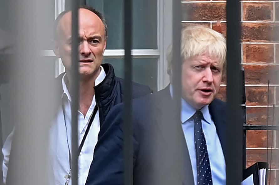 Boris Johnson and his special advisor Dominic Cummings leave from the rear of Downing Street before heading to the Houses of Parliament on 3 September.