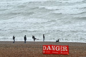 People throw pebbles on a blustery beach in Brighton