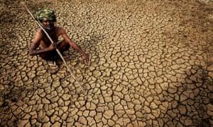 A farmer sits on his dried-up land near Andhra Pradesh