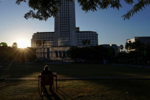 A homeless man sits in the morning sun in downtown Los Angeles in front of city hall.