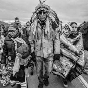 Chief Arvol and Paula Looking Horse and other water protectors walking away from a meeting with law enforcement on the Backwater Bridge at Standing Rock, with a prayer song.