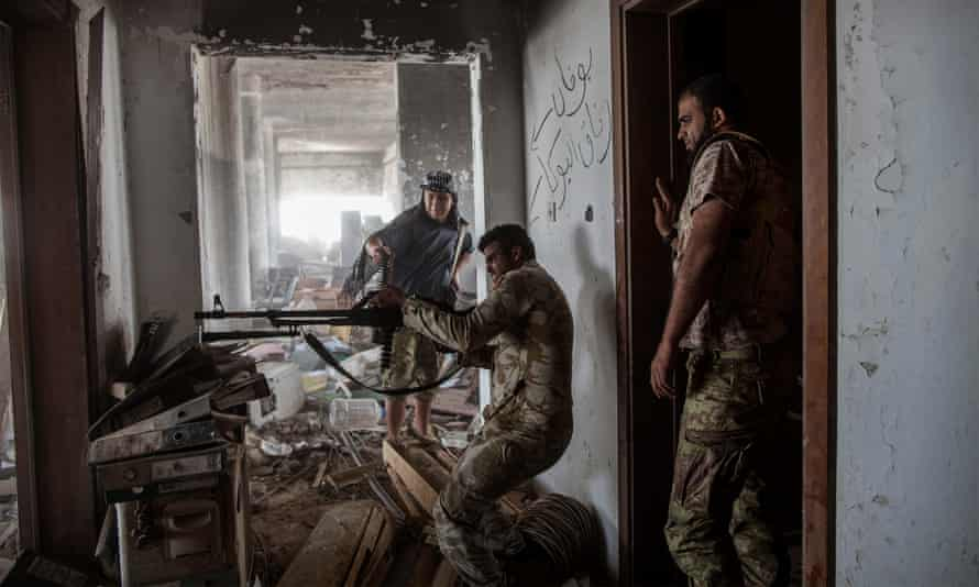 A fighter loyal to Libya's Government of National Accord fires his weapon during fighting against Isis in Sirte.