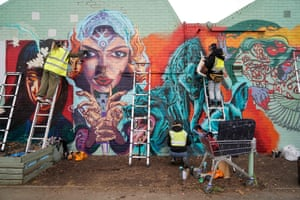 Members of the Wom Collective, a female street art collective, work on their new piece of street art in Brixton to celebrate International Women's Day, in London, England