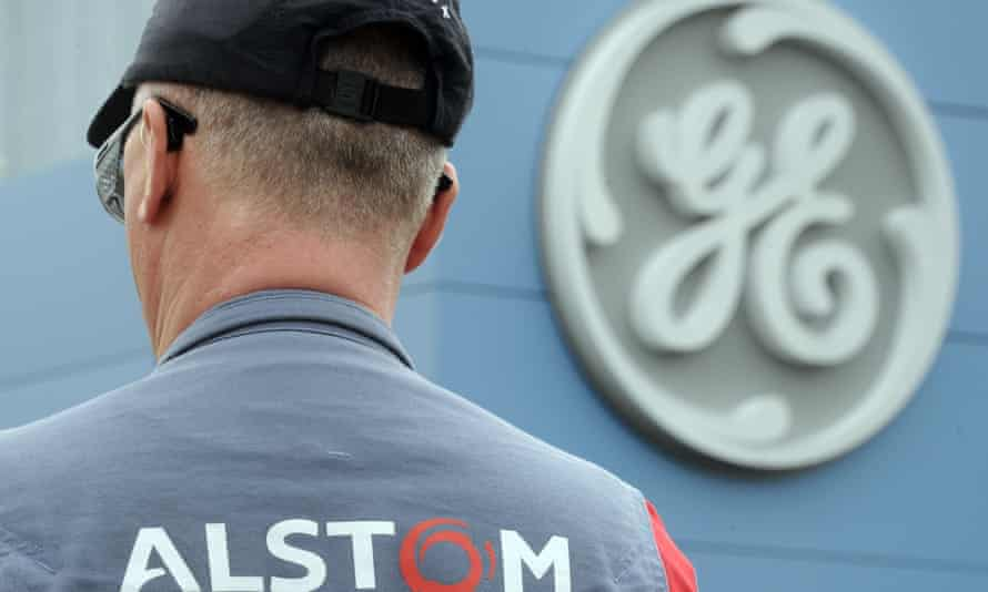 Alstom worker standing in front of the General Electric logo