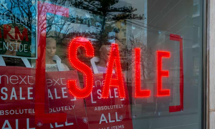 A sale sign adorns a shop window.