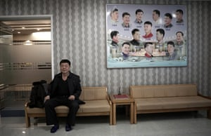 A man waits outside a barber shop in Pyongyang. The poster beside him shows the types of hairstyles worn by men in North Korea