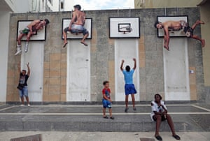 Havana, Cuba: Children play basketball beneath an installation by the Spanish artists Martín and Sicilia during the 13th Havana Biennial art exhibition