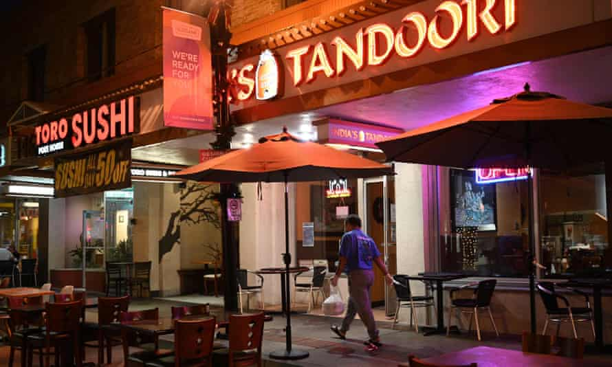 A man carries a package of take-out food as he walks past temporary outdoor restaurant seating last month in Burbank.