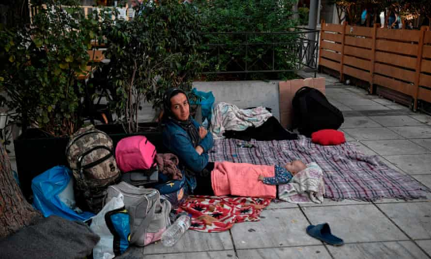 A refugee Afghan mother sits with her three-month-old baby girl in Victoria Square, Athens.