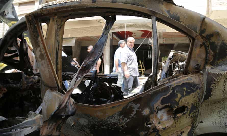 People walk past a burnt vehicle at the site of a supected suicide bombing in Syria.