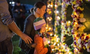 A young girl is guided to place a candle on a flower wall as part of an Amnesty international vigil in Sydney.