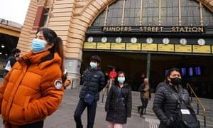 People wearing masks leave mebourne's flinders street station
