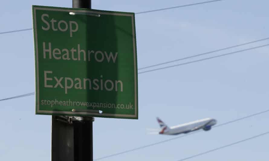 A British Airways plane flies past a protest sign put up by a local campaign group in Harmondsworth village