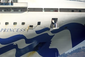 Crew members wear masks while preparing to dock the Grand Princess in Oakland.
