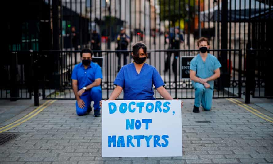 Three doctors in scrubs and masks kneeling outside the Downing Street gates with one holding a placard reading 'Doctors Not Martyrs'