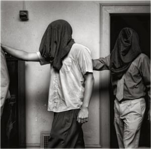 This photograph of hooded inductees recalls images of prisoners being degraded at Abu Graibh.