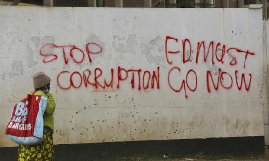 A woman in Zimbabwe walks past a wall with graffiti calling on the government to stop corruption June 2020.