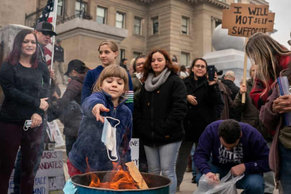 A child tosses a surgical mask into a fire at a protest outside the Idaho statehouse in Boise in March.