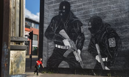 a young boy runs past a loyalist paramilitary mural in Belfast, Northern Ireland.