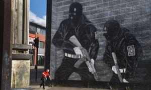 A young boy runs past a loyalist paramilitary muralin Belfast.