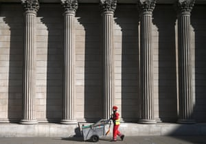 A street cleaner passes the Bank of England in the City of London.