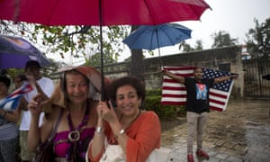 Cubans gather along the Malecón sea wall to see the Obamas