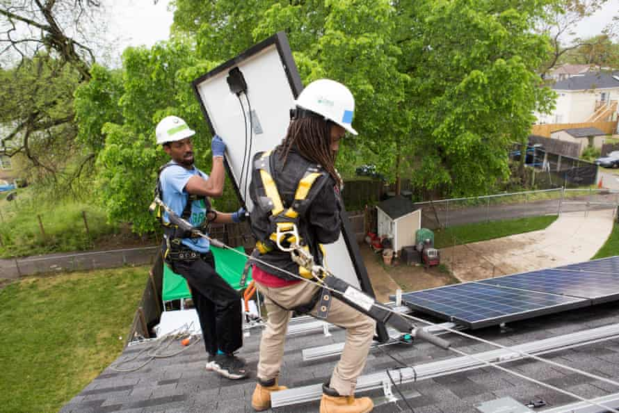 Antwain Nelson (left) and Andre Hinton (right), both workers with Grid Alternatives, install a solar panel at a home in Washington DC in May 2016.