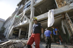 A member of the French organisation Pompiers de l'urgence walks out of the heavily damaged Mercure hotel in Palu.