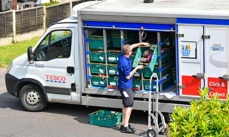 a tesco home delivery van driver unloads his vehicle