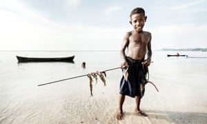 A boy shows his catch of speared fish