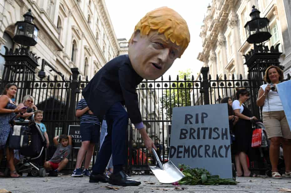 A protester dressed as Boris Johnson digs a grave outside Downing Street on 28 August.