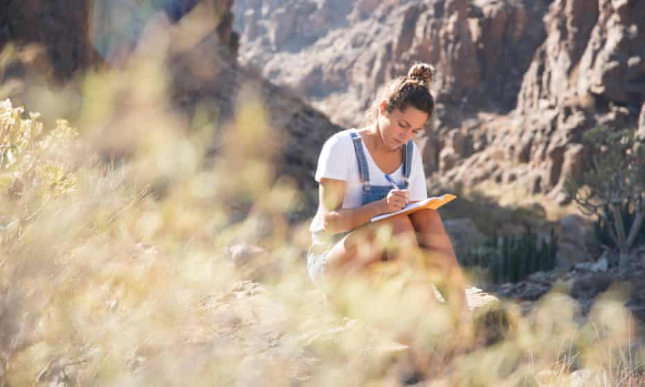Young female hiker writing notes in rocky valley