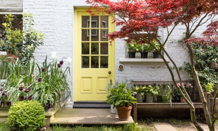 A yellow front door with glass panels in a pale grey brick home with a profusion of plants around
