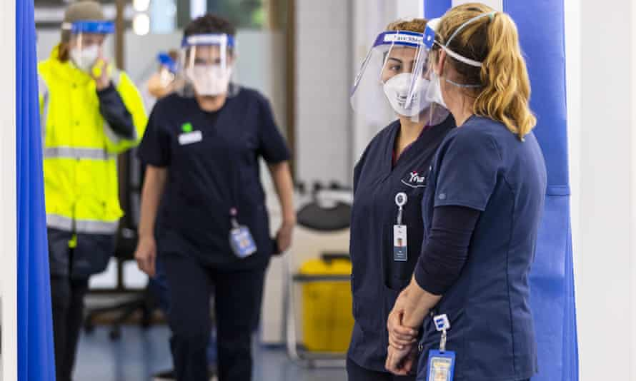 Health care workers are seen in the COVID vaccination hub in hospital.