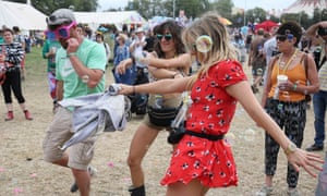 Festival fans with bumbags dance at Glastonbury.