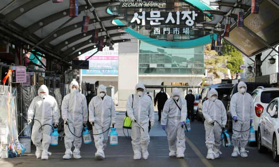 Coronavirus outbreak: workers spray a market in Daegu, the centre of the South Korea infections, on Sunday.