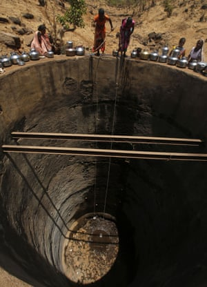 Women try to draw drinking water from a small puddle, all that remains at the bottom of a well in Bhakrecha Pada, Maharashtra