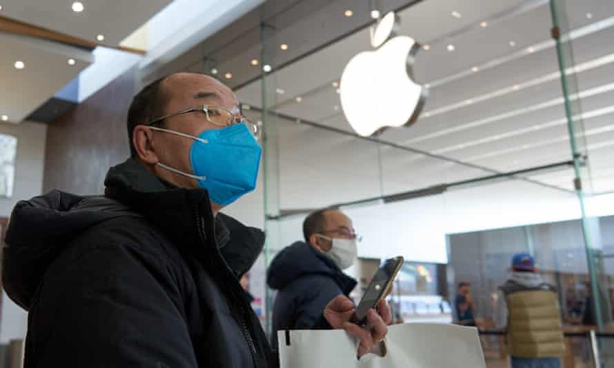 People wearing face masks walk past an Apple store in Brossard, on the south shore of Montreal, Canada