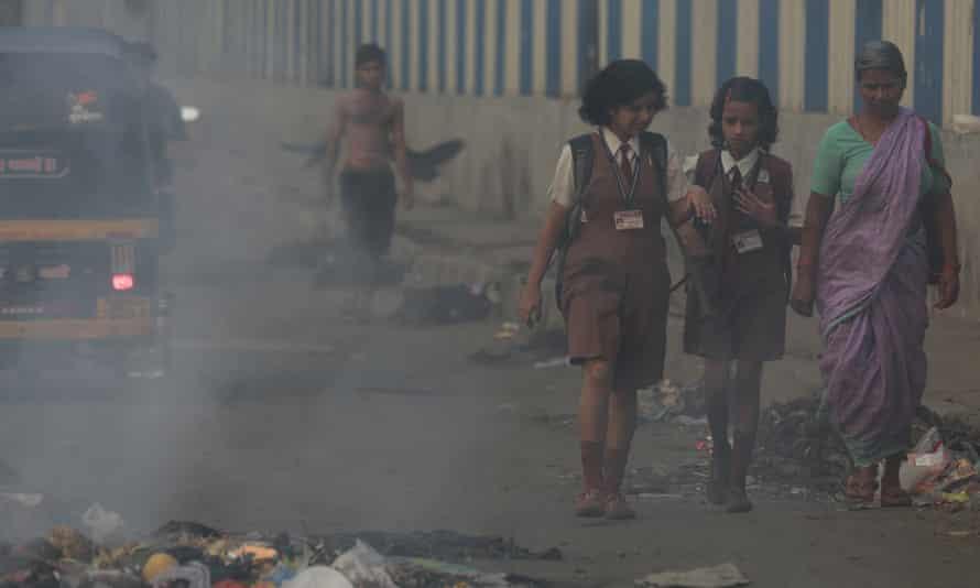 Schoolgirls walk past burning rubbish